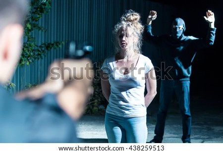 Victim of a kidnapping standing between the assaulter and a policeman aiming a gun at him - stock photo