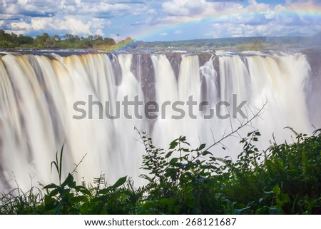 Victoria Falls, a frontal view with a rainbow through the mist and spray. - stock photo