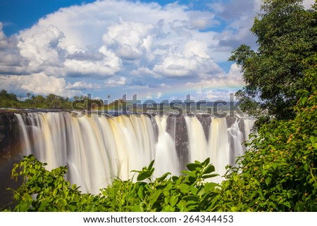 Victoria Falls.  Frontal view with a rainbow.  Taken with an MD filter.  Blue sky with clouds looming. - stock photo