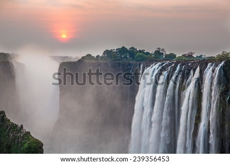 Victoria Falls sunset with red sun, View from Zambia - stock photo