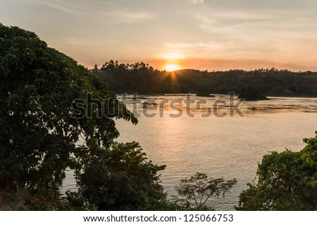 Victoria Nile River at sunset with bright Sun reflecting in water against evening glow background. Jinja, Uganda, Eastern Africa. - stock photo