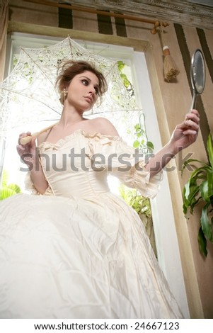 Victorian beautiful woman, white dress at home looking hand mirror - stock photo