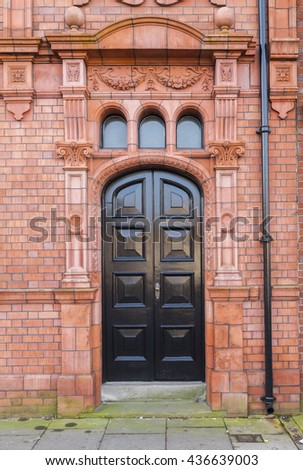 Victorian door surrounded by ornate red brick with decorative terracotta tiles. - stock photo