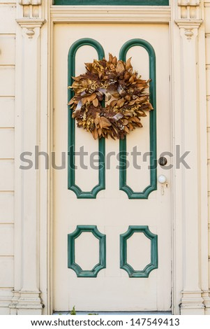 Victorian style wooden door with rustic wreath - stock photo