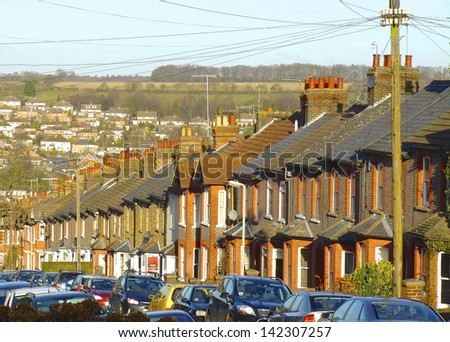 Victorian terrace in suburban England going down a steep valley. - stock photo