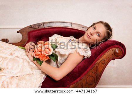 Victorian woman with flowers on fainting couch - stock photo