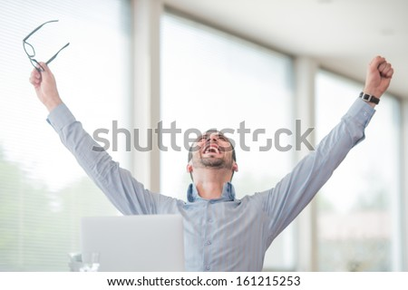Victorious corporate man celebrating with his arms lifted in the air - stock photo