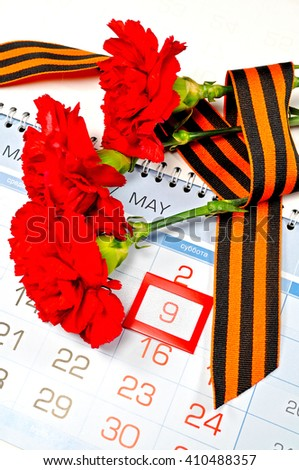 Victory Day 9 May card - three red carnations wrapped with George ribbon on the calendar with 9 May date- holiday commemorating  victory of Soviet Union in the Great Patriotic War. 9 May concept.  - stock photo