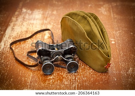 Victory Day on May 9. Vintage military binoculars and a field cap with a red star - stock photo