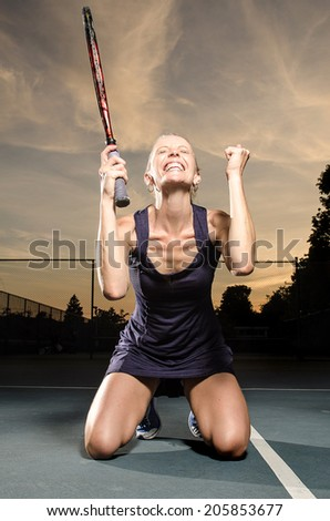 Victory female tennis player - stock photo