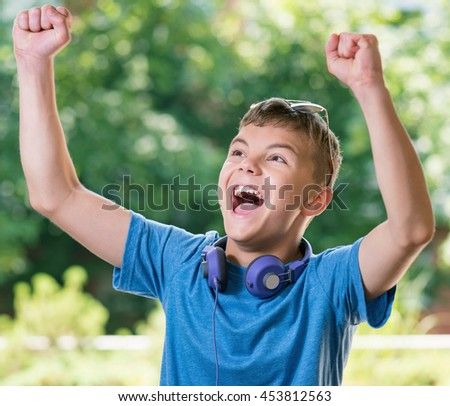 Victory screaming teen boy 12-14 year old. Winner boy with headphones and sunglasses posing outdoors. - stock photo
