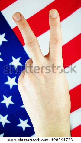 Victory sign against the US flag  - stock photo