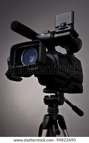 Video camera and tripod on gray background - stock photo