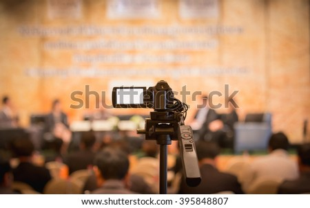 video camera in business conference room recording participants and speaker - stock photo