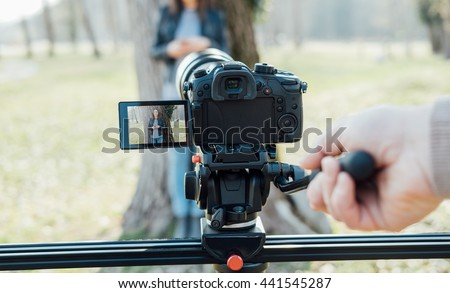 Video shooting at the park: video camera and operator hand on foreground and female model standing in the background - stock photo