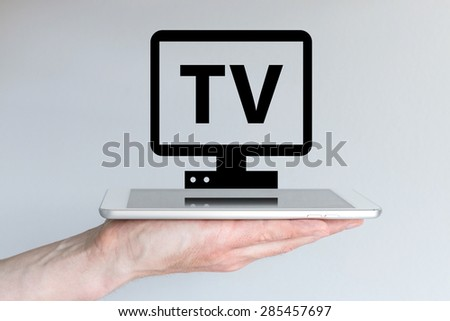 Video streaming and internet TV concept with smart phone or tablet. Hand holding modern white tablet or smart phone in front of blurred grey background. Black television icon.  - stock photo