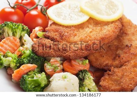 Viener schnitzel, breaded steak with grated vegetables - stock photo