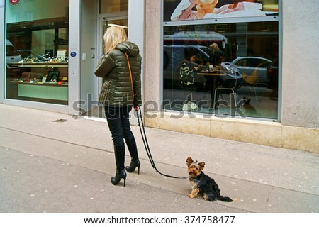 VIENNA, AUSTRIA - FEBRUARY 4, 2016: Young woman with mobile phone and dog on streets of Vienna                      - stock photo