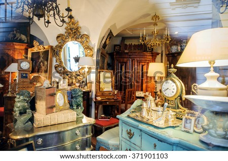 VIENNA, AUSTRIA - JULY 4, 2011: Antiquities shop window shopping seen from the street - Kohlmarkt street in Vienna. The vintage store sells old clocks, old mirrors, old furniture, vintage objects - stock photo