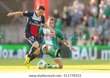 VIENNA, AUSTRIA - JULY 12 Christopher Dibon (#17 Rapid) and Kevin Gameiro (#19 Paris) fight for the ball at a friendly soccer game on July 12, 2013 in Vienna, Austria. - stock photo