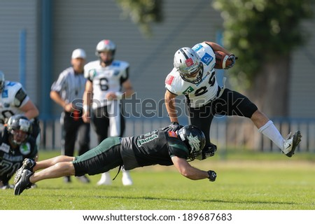 VIENNA,  AUSTRIA - JUNE 8 DB Schahin Gholami (#21 Dragons) tackles RB Andreas Hofbauer (#29 Raiders) during the AFL football game on June 8, 2013 in Vienna, Austria. - stock photo