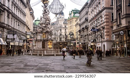 VIENNA, AUSTRIA - NOVEMBER 26, 2013: City center Graben street with shops and restaurants full of people with christmas decorations. Pestsaule sculpture showing the Holy Trinity on a corinthian column - stock photo