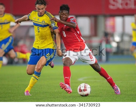 VIENNA, AUSTRIA - SEPTEMBER 9, 2014: Albin Ekdal (#8 Sweden) and David Alaba (#8 Austria) fight for the ball in an European Championship qualifying game. - stock photo