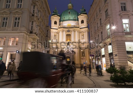 VIENNA, AUSTRIA - 20TH DECEMBER 2015: Catholic Church of St. Peter at Night. A horse  and chariot and people can be seen. - stock photo