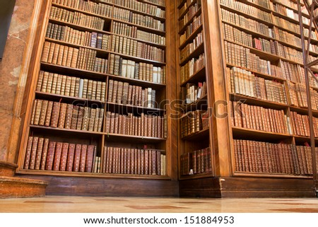 VIENNA - JUNE 1: Old wooden bookcase of Austrian National Library filled with books on various areas of science on June 1 2013 in Austria. The largest library in Austria with 7.4 million items. - stock photo