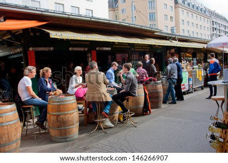 VIENNA - JUNE 6: People drink wine and sit around the barrels near the small shop of market Naschmarkt on June 6, 2013 in Vienna, Austria. The popular Naschmarkt has existed since the 16th century. - stock photo