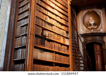 VIENNA - JUNE 1: Thousands of old books in a cabinet near the ancient bust in the old Austrian National Library on June 1, 2013 in Austria. The largest library in Austria with 7.4 million items  - stock photo