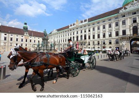 VIENNA - SEPTEMBER 5: Tourists enjoy their horse-drawn carriage ride on September 5, 2011 in Vienna. As of 2008, Vienna was the 20th most visited city worldwide (by international visitors). - stock photo