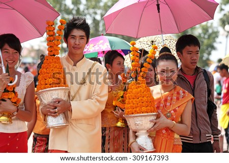 VIENTIANE, LAOS - NOV 20: Unidentified many people phan holding flowers arranged in lotus-shape walk around Pha That Luang on Nov 20, 2010 It is celebrated 450th year founding anniversary of Vientiane - stock photo