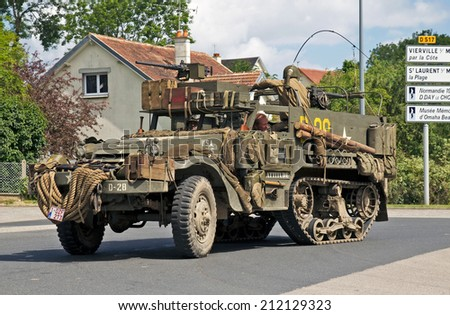 VIERVILLE-SUR-MER, FRANCE - JUNE 5: A vintage WW2 US army halftrack heads away from Omaha beach during the celebrations of the 70th D-Day landings anniversary on June 5, 2014 in Vierville-sur-mer - stock photo