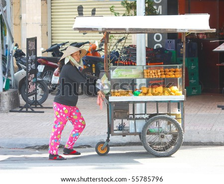 VIETNAM - JUNE 10: A Vietnamese bread stall owner pushes her make shift wagon stall along the streets. June 10, 2010 Ho Chi Minh City, Vietnam - stock photo