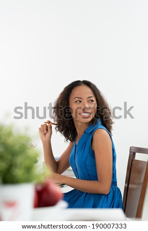 Vietnamese brunette sitting at the table - stock photo