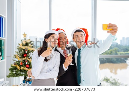 Vietnamese business team taking selfie at the Christmas party - stock photo