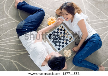 Vietnamese couple lying on the floor and playing chess - stock photo