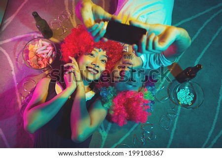 Vietnamese couple taking a selfie at the party - stock photo