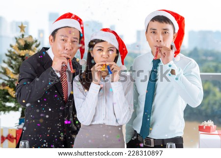Vietnamese coworkers with party blowers celebrating Christmas - stock photo