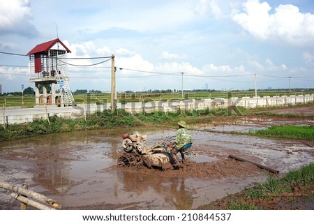 Vietnamese farmer handling a tractor in the paddy field in a rural area of Hanoi at the beginning of a new season. - stock photo