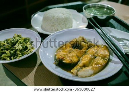Vietnamese food lunch: com ca basa kho to. Two fish steaks, braised veggies, rice and soup. Chopsticks on plates - stock photo