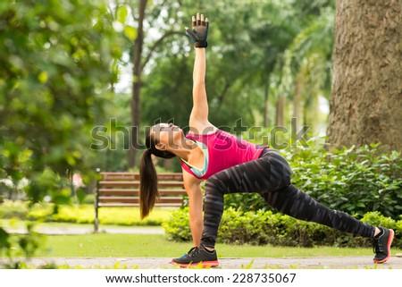 Vietnamese girl exercising in park doing revolved side angle pose - stock photo