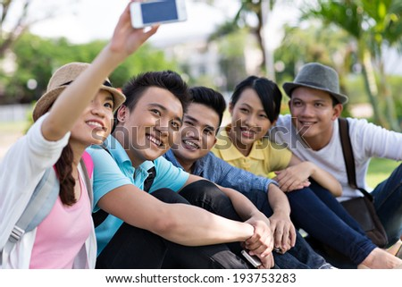 Vietnamese girl taking a picture with her friends - stock photo
