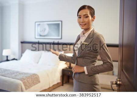 Vietnamese hotel customer service representative showing double room - stock photo