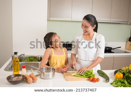 Vietnamese mother and daughter cooking together - stock photo