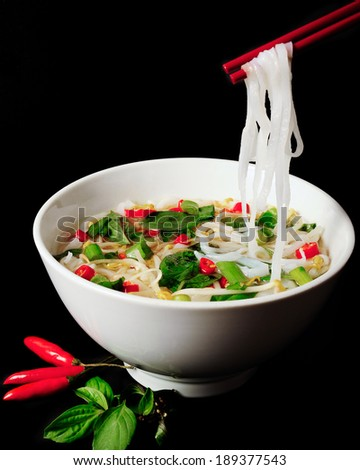 Vietnamese Pho Noodle Soup. Beef with Chilli, Basil, Rice Noodles, Bean Shoots showing noodles picked up with Chopsticks on a black background. - stock photo