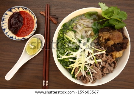 Vietnamese rice noodles are served with beef, lime, bean sauce and chili sauce and ready to eat. - stock photo