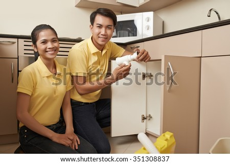 Vietnamese service team cleaning clogged sink - stock photo