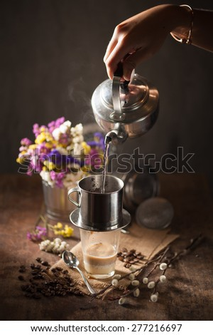 Vietnamese style drip coffee, Woman hand pouring hot water into metal coffee filter with low key scene - stock photo